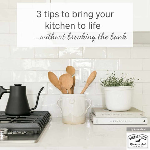 """Blog cover displaying kitchen space with black metal stove top, a matte black coffee pot, cookery books, a pot plant, a storage piece with wooden spoons in it and a white tiled accent wall. Blog header on cover says, """"3 tips to bring your kitchen to life without breaking the bank."""" Interior design blog Written by vintage-etc in Cape Town. We make custom made & bespoke tables, benches, free-standing kitchen islands, desks, media units & wardrobes in our Cape Town & Johannesburg workshops – using Oak, Oregon, Ash, Beech, Birch Ply & Meranti. We also sell imported furniture, provide design consulting services & make soft furnishings e.g. sofas & upholstered chairs in linen, velvet & stain resistant fabric."""
