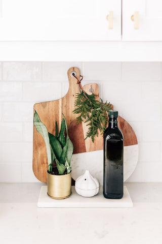 White Kitchen with green Snake Plant, Olive Oil, a garlic shaped container and two wooden chopping/cutting boards. Interior design blog about our tips on bringing your kitchen to life without spending too much money. Written by vintage-etc in Cape Town. We make custom made & bespoke tables, benches, free-standing kitchen islands, desks, media units & wardrobes in our Cape Town & Johannesburg workshops – using Oak, Oregon, Ash, Beech, Birch Ply & Meranti. We also sell imported furniture, provide design consulting services & make soft furnishings e.g. sofas & upholstered chairs in linen, velvet & stain resistant fabric.
