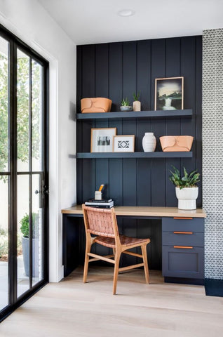 Deep dark blue paneling on wall of home office with wood chair, wood flooring, glass sliding doors and shelving. Interior design blog written by Vintage-etc about how wood paneling is the next big trend for living rooms, bedrooms, ceilings, entrance hallways and many more. Get this look with Vintage-etc. We make custom made & bespoke tables, benches, free-standing kitchen islands, desks, media units & wardrobes in our Cape Town & Johannesburg workshops - using Oak, Oregon, Ash, Beech, Birch Ply & Meranti. We also sell imported furniture, provide design consulting services & make soft furnishing e.g. sofas & upholstered chairs in linen, velvet & stain resistant fabric