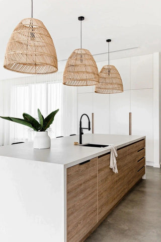 White kitchen with white cupboards, wooden woven light chandeliers, a green plant and a white free-standing kitchen island with wooden drawers/cabinets. Interior design blog about our tips on bringing your kitchen to life without spending too much money. Written by vintage-etc in Cape Town. We make custom made & bespoke tables, benches, free-standing kitchen islands, desks, media units & wardrobes in our Cape Town & Johannesburg workshops – using Oak, Oregon, Ash, Beech, Birch Ply & Meranti. We also sell imported furniture, provide design consulting services & make soft furnishings e.g. sofas & upholstered chairs in linen, velvet & stain resistant fabric.