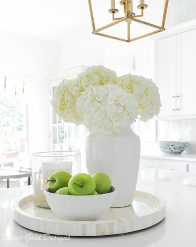 Display in kitchen with white cabinets and counter tops – there is a cream/white tray on the counter with 3 White cluster of flowers in a white vase, green apples in a white fruit bowl and a candle in a glass container. Interior design blog about our tips on bringing your kitchen to life without spending too much money. Written by vintage-etc in Cape Town. We make custom made & bespoke tables, benches, free-standing kitchen islands, desks, media units & wardrobes in our Cape Town & Johannesburg workshops – using Oak, Oregon, Ash, Beech, Birch Ply & Meranti. We also sell imported furniture, provide design consulting services & make soft furnishings e.g. sofas & upholstered chairs in linen, velvet & stain resistant fabric.