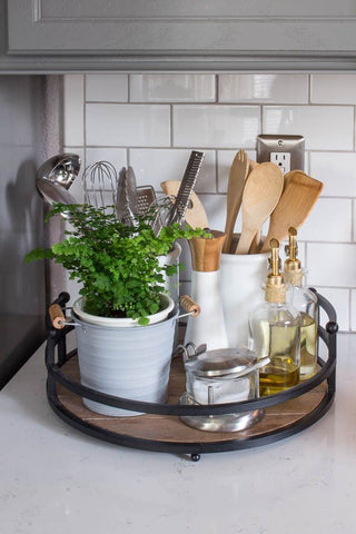 Wooden tray displaying salt container, a pot plant, a storage container/pot with utensils and wooden spoons, Olive Oil and vinegar and pepper. Interior design blog about our tips on bringing your kitchen to life without spending too much money. Written by vintage-etc in Cape Town. We make custom made & bespoke tables, benches, free-standing kitchen islands, desks, media units & wardrobes in our Cape Town & Johannesburg workshops – using Oak, Oregon, Ash, Beech, Birch Ply & Meranti. We also sell imported furniture, provide design consulting services & make soft furnishings e.g. sofas & upholstered chairs in linen, velvet & stain resistant fabric.