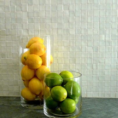Two glass fruit bowls in kitchen displaying yellow lemons and green limes with a white textured tiled on accent wall in the background. Interior design blog about our tips on bringing your kitchen to life without spending too much money. Written by vintage-etc in Cape Town. We make custom made & bespoke tables, benches, free-standing kitchen islands, desks, media units & wardrobes in our Cape Town & Johannesburg workshops – using Oak, Oregon, Ash, Beech, Birch Ply & Meranti. We also sell imported furniture, provide design consulting services & make soft furnishings e.g. sofas & upholstered chairs in linen, velvet & stain resistant fabric.