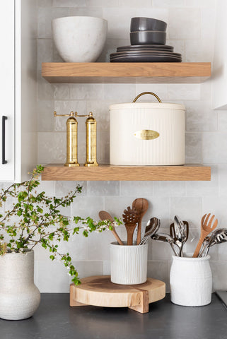 White textured tiled kitchen wall with Solid Oak floating shelves displaying bowls and a bread bin. Underneath the floating shelves on the black counter top are wooden spoons and metal utensils in a white pot and a pot plant in a ceramic pot. Interior design blog about our tips on bringing your kitchen to life without spending too much money. Written by vintage-etc in Cape Town. We make custom made & bespoke tables, benches, free-standing kitchen islands, desks, media units & wardrobes in our Cape Town & Johannesburg workshops – using Oak, Oregon, Ash, Beech, Birch Ply & Meranti. We also sell imported furniture, provide design consulting services & make soft furnishings e.g. sofas & upholstered chairs in linen, velvet & stain resistant fabric.