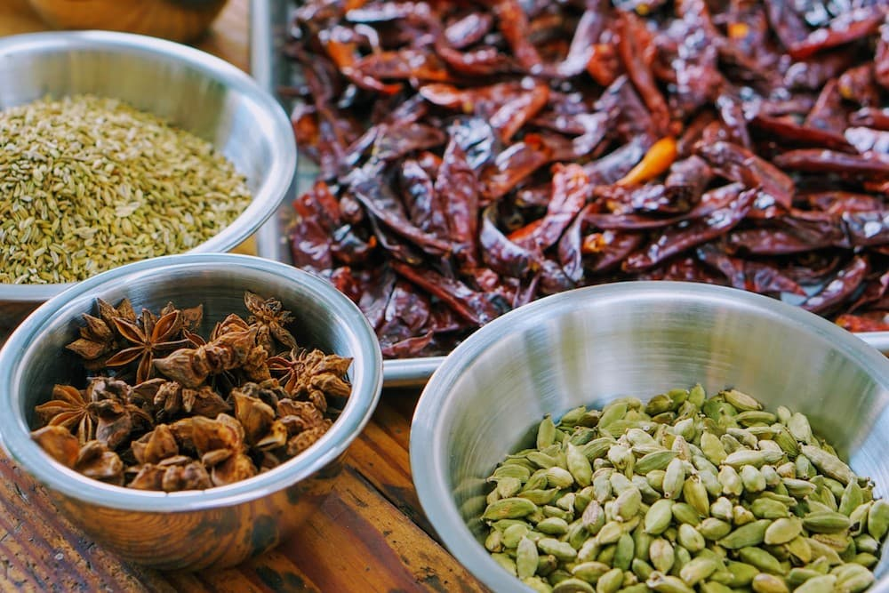 Whole spices star anise cardamom fennel seeds in bowls
