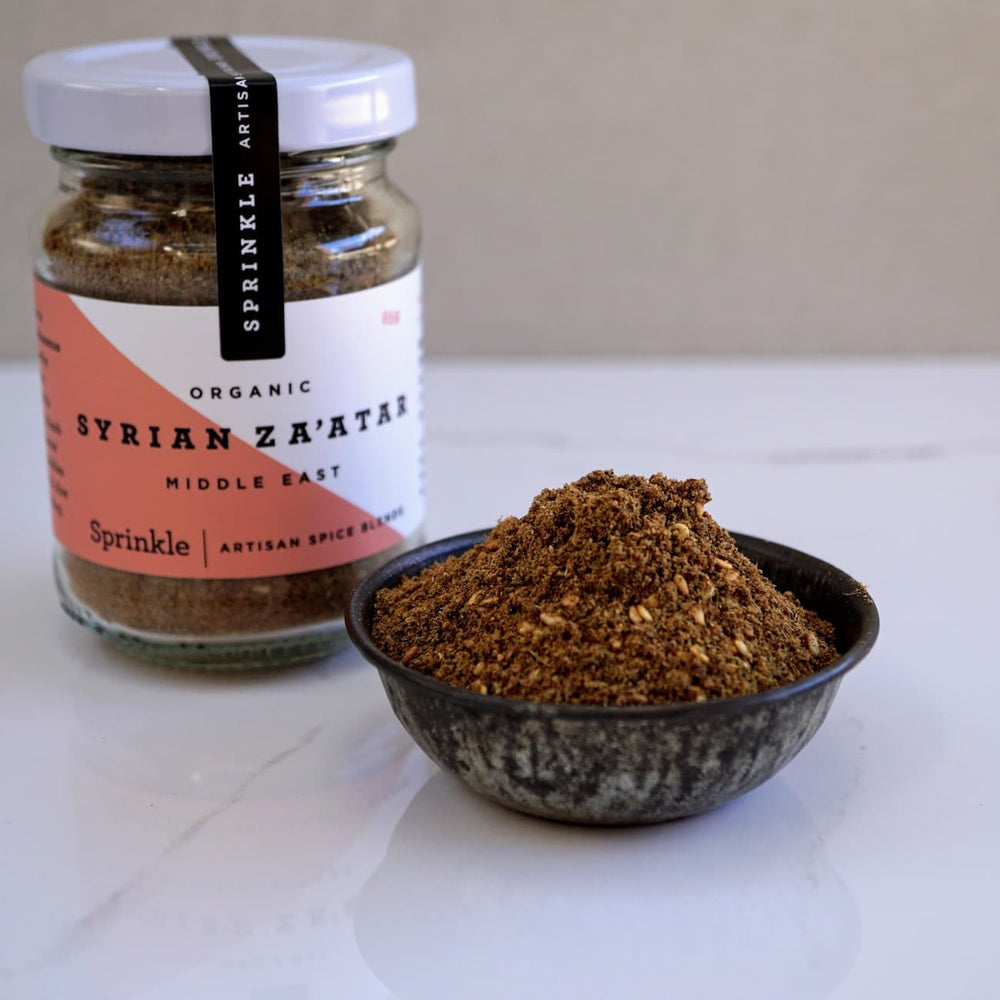 Jar of Syrian Za'atar spice blend and bowl of spices on a white marble surface