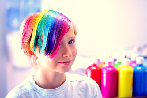 Young boy celebrating his uniqueness with creative hair colours