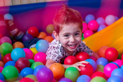 Wellbeing articles - Happy boy playing in a children's ball pit
