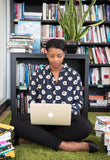 Woman in a library on a laptop; help reboot your career with research and skill and knowledge updates