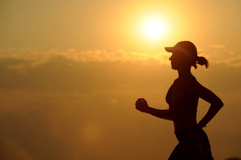 Woman at sunset, running for health and fitness
