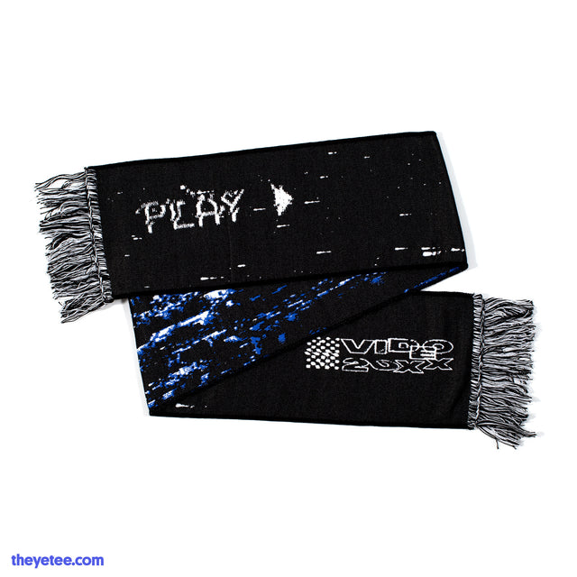 Two sided scarf with black and white fringes at the ends. One side is black with the play logo at one end and the VIDEO 20XX logo at the other end. The other side is white, blue and black television static. - VHS Scarf