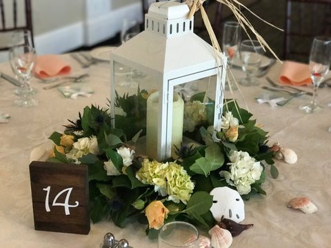 Lantern centerpieces with floral wreaths around done by Gig Morris Florist in Belmar, NJ at the Berkely Hotel in Asbury Park, NJ with hydrangea and seashells to make a seashore look.