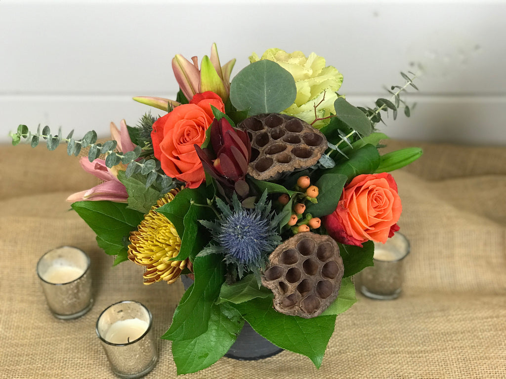Another warm, rustic design. Similar to the Centerpiece design of Regina's Rustic Thanksgiving but in a smaller more versatile container. Still filled with warm tones and texture including lilies, hydrangea, kale, thistle, eucalyptus, roses, leucadendron, and hypericum.  Instead of the traditional long and low design, this cylinder tin allows for multiple down the table or spread throughout the house.  Done by Gig Morris Florist in Belmar, New Jersey.