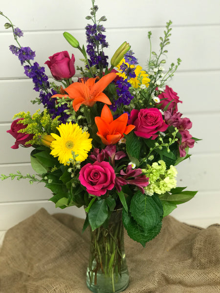 tall vase with wildflowers that include lilies, Larkspur, Gerber daisies, roses, and green hydrangea