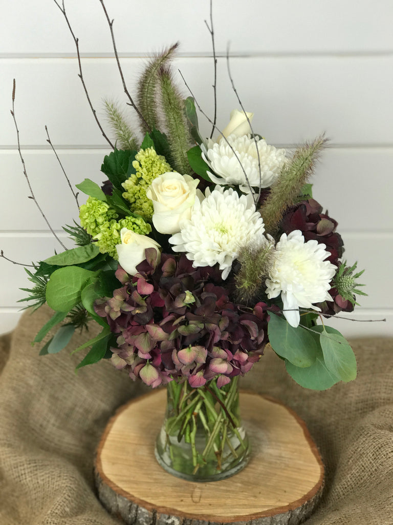 A floral arrangement in a vase of flowers that include hydrangea, mums, roses, for a fall look from a local flower shop in Belmar, New Jersey Gig Morris Florist