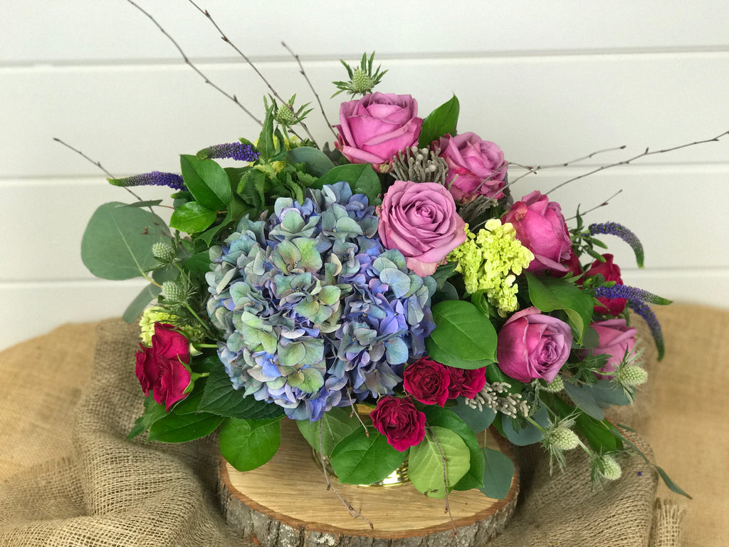 Custom centerpiece arrangement of florals that include flowers like hydrangea, roses, spray roses