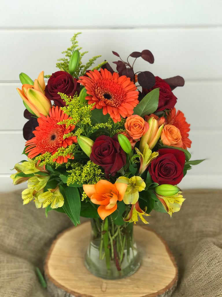 Fall flowers in vase arrangement. Roses, Gerber daisies, lilies in oranges, reds, and yellows