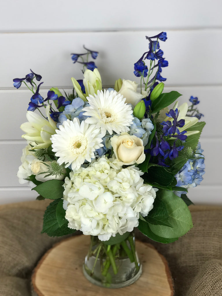 white and blue flowers create a sense of the beach with florals that include hydrangea, Gerber daisies, delphinium, lilies, roses and thistle