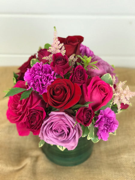 Roses in pinks, lavenders, purples, reds in vase arrangement by a flower shop in Belmar, New Jersey