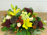 Thanksgiving floral centerpiece for a table from Gig Morris Florist in Belmar, New Jersey. Consists of fall colors with mums, lilies, hydrangea, roses, and magnolia leaves