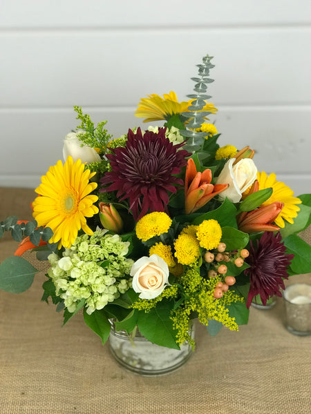 Thanksgiving Day flowers done by Gig Morris Florist in Belmar, New Jersey traditional Thanksgiving centerpiece; a modern cylinder glass vase overflowing with Fall flowers such as lilies, gerber daisies, hydrangea, mums, roses and eucalyptus