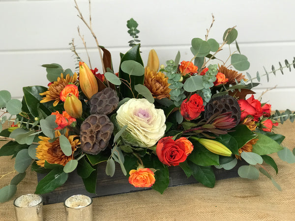 "A natural wooden box is used beautifully as the vessel for this centerpiece. Filled with hues of the Fall and textures found throughout nature, it is a perfect adornment to your Thanksgving Day table.  The long and low centerpiece sits in a 18"" wooden box which contains florals such as roses, spray roses, kale, hypericum, mums, lilies, leucadendron, magnolia, and eucalyptus. A stunner, to say the least! by gig Morris florist in belmar, New Jersey"