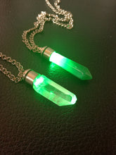 green kyber crystal pendants turned on