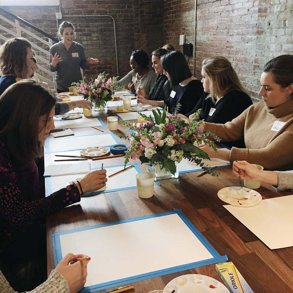 women painting using watercolors during level up class