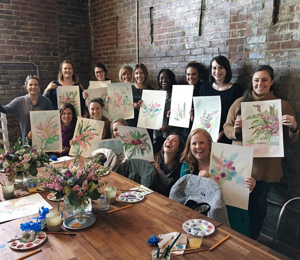women having a good time showing finished floral watercolor project