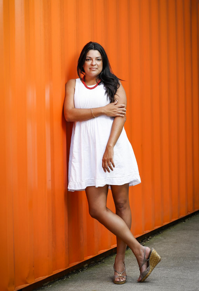 natalia bishop wearing white dress and red necklace in front of orange wall at Copper & King Distillery in Louisville, Ky