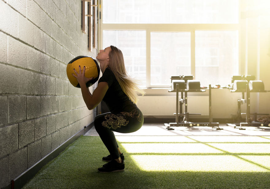 woman doing an exercise with a heavy medicine ball
