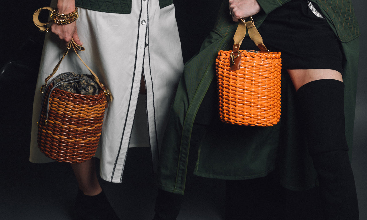Women holding designer bucket bags made from woven material