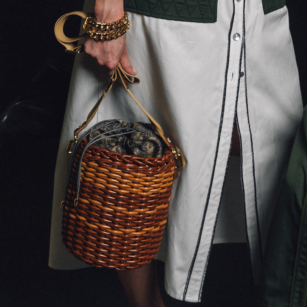 Woman holding designer bucket bag made from brown & orange woven material