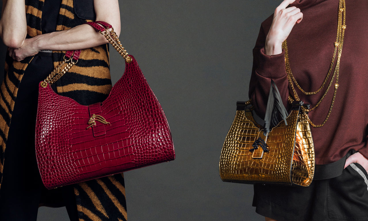 Women holding luxury handbags. Hobo-style handbags are red and metallic gold.