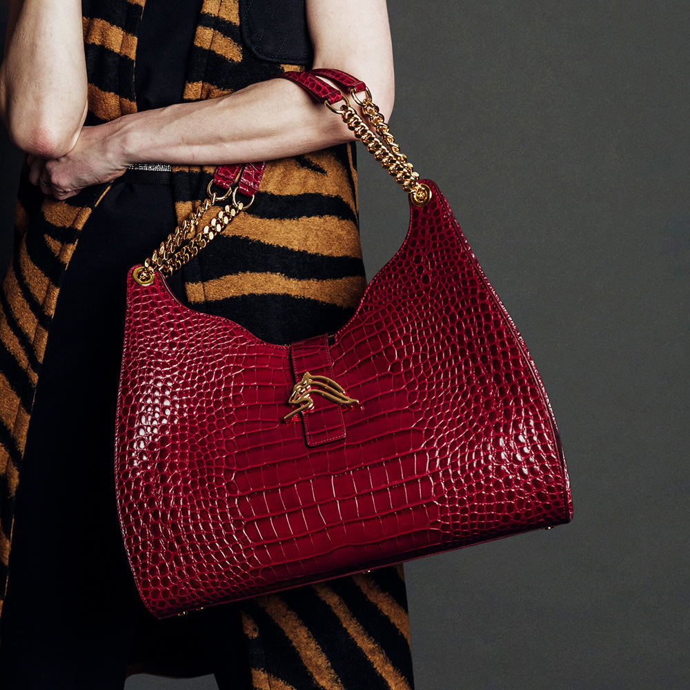 Woman holding luxury handbags. Hobo-style handbag is red crocodile-embossed leather.