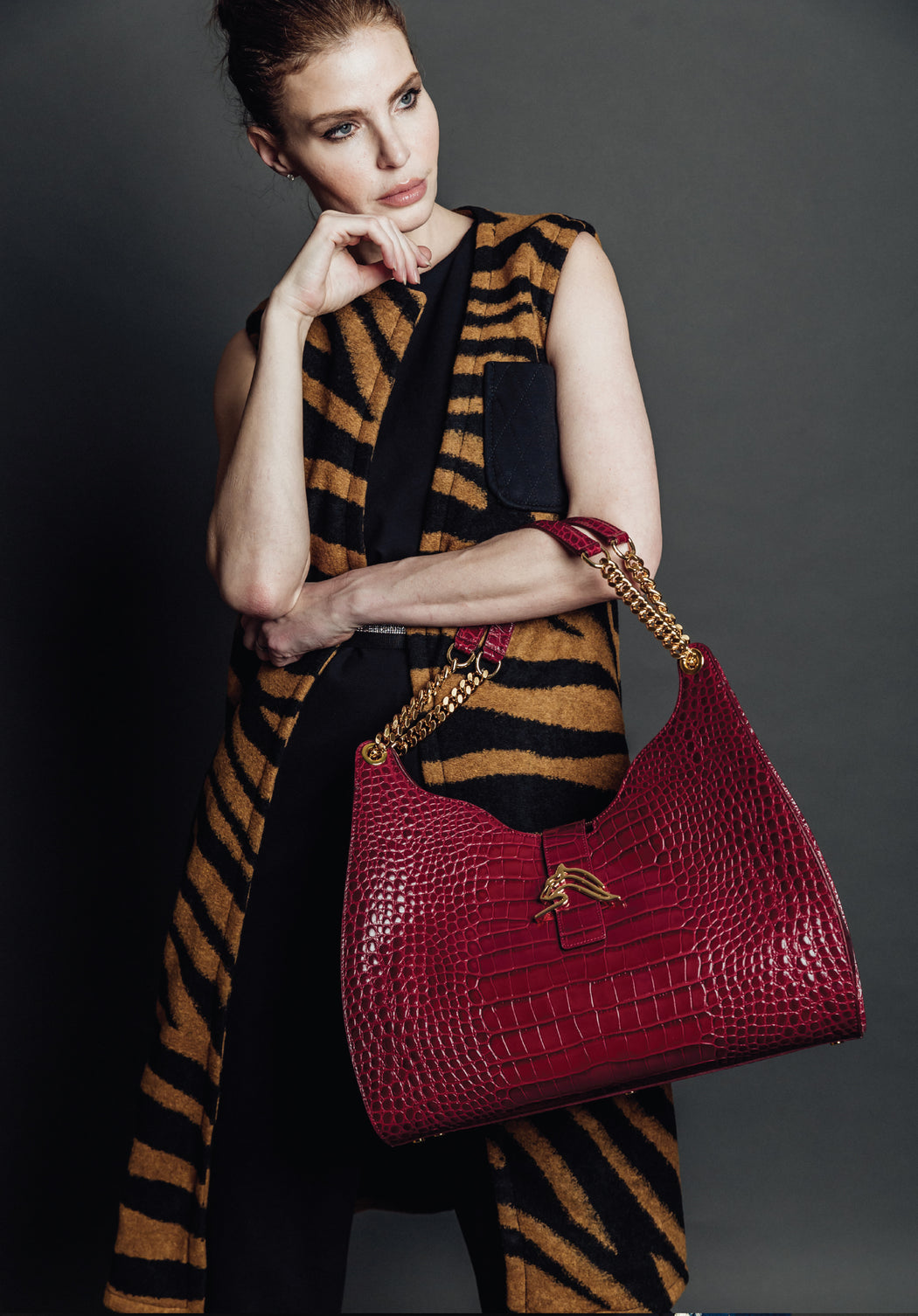 Woman with designer hobo bag in croc-embossed leather in bordeaux color