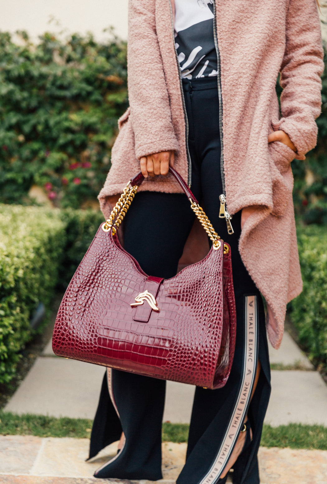 Woman holding a bordeaux-colored designer hobo bag in croc-embossed leather