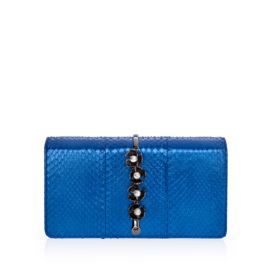 This fold-over style luxury clutch bag in cobalt elaphe is a smaller size, sitting upon a beautiful brass vine and embellished with elegant pearl stones. This roomy clutch is comfortable to hold and easily fits everything you need. Magnetic top closure. Handmade in Italy.