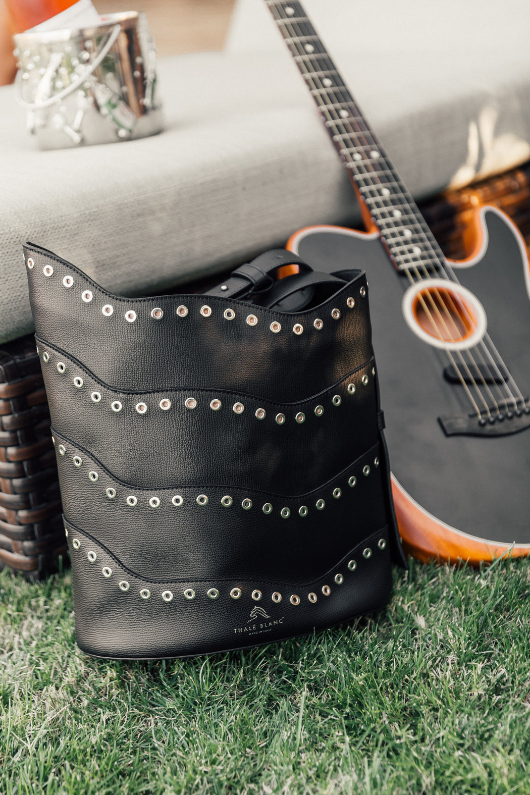 Luxury handbag: Black bucket purse on floor next to guitar