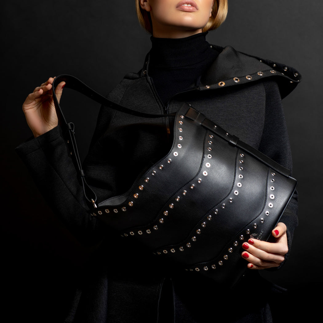Woman holding a designer bucket bag in black leather with silver eyelets