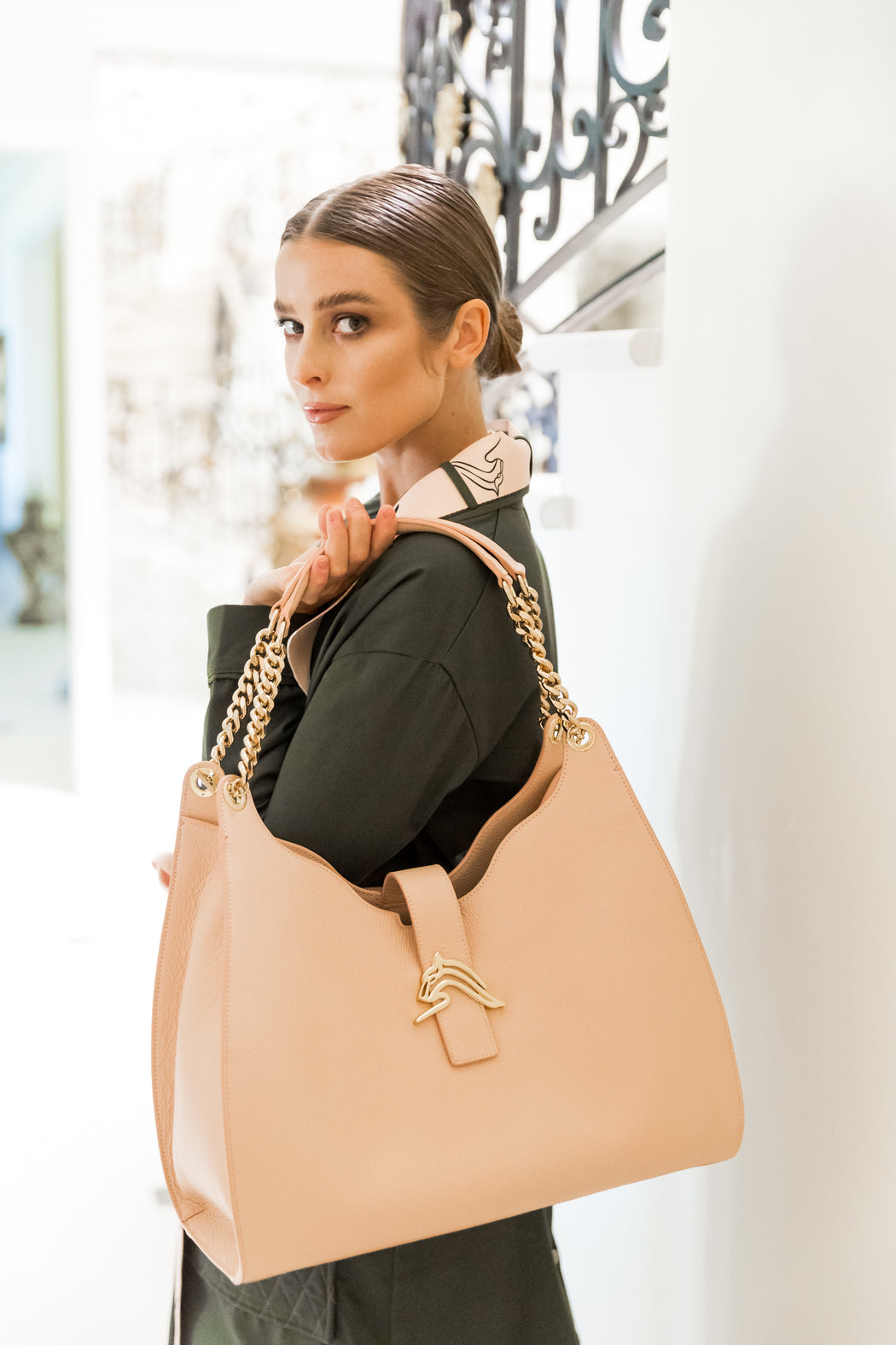 Woman carrying a designer hobo bag in nude-pink leather