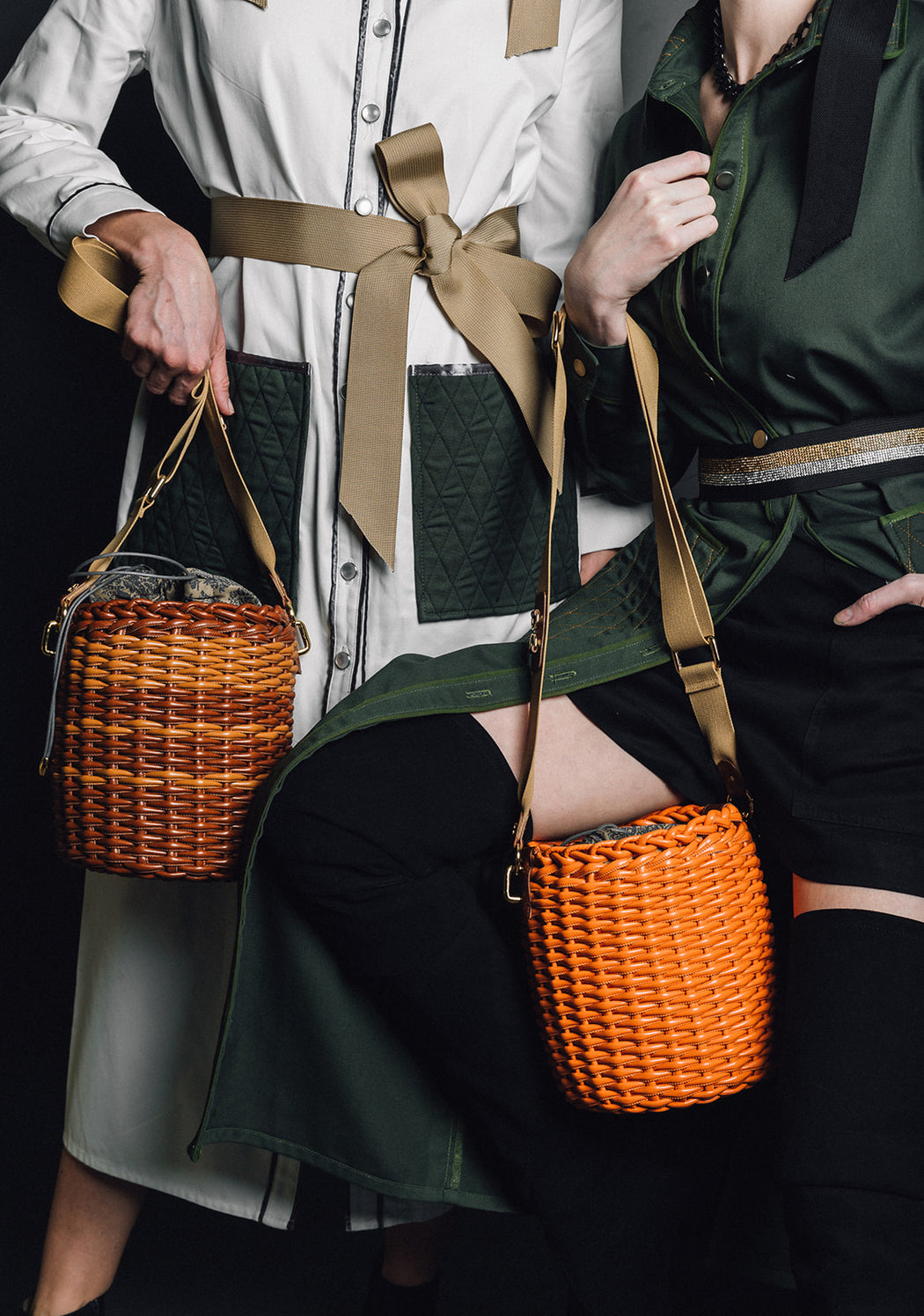 Two women holding basket weave purses with vegan leather trim