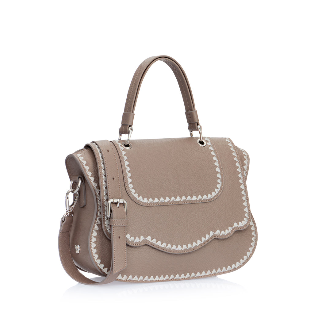 An instant statement luxury leather bag in taupe grained calfskin, the feminine curved lines and spacious interior ensures that the bag is both chic and functional. Can be comfortably worn on the shoulder as it features a removable shoulder strap. The signature curved flap is highlighted with beautiful ivory silk tulip contrast stitching.