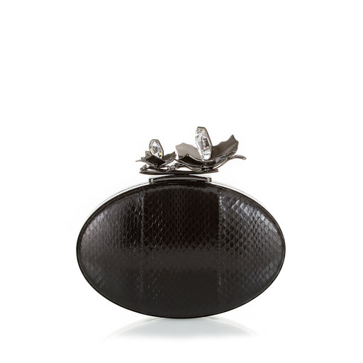 An edgy luxury evening clutch, the Oval Bloom features a gunmetal orchid and crystal stones, set against rich black watersnake. A detachable wrist chain is included. Designed to fit just the essentials.