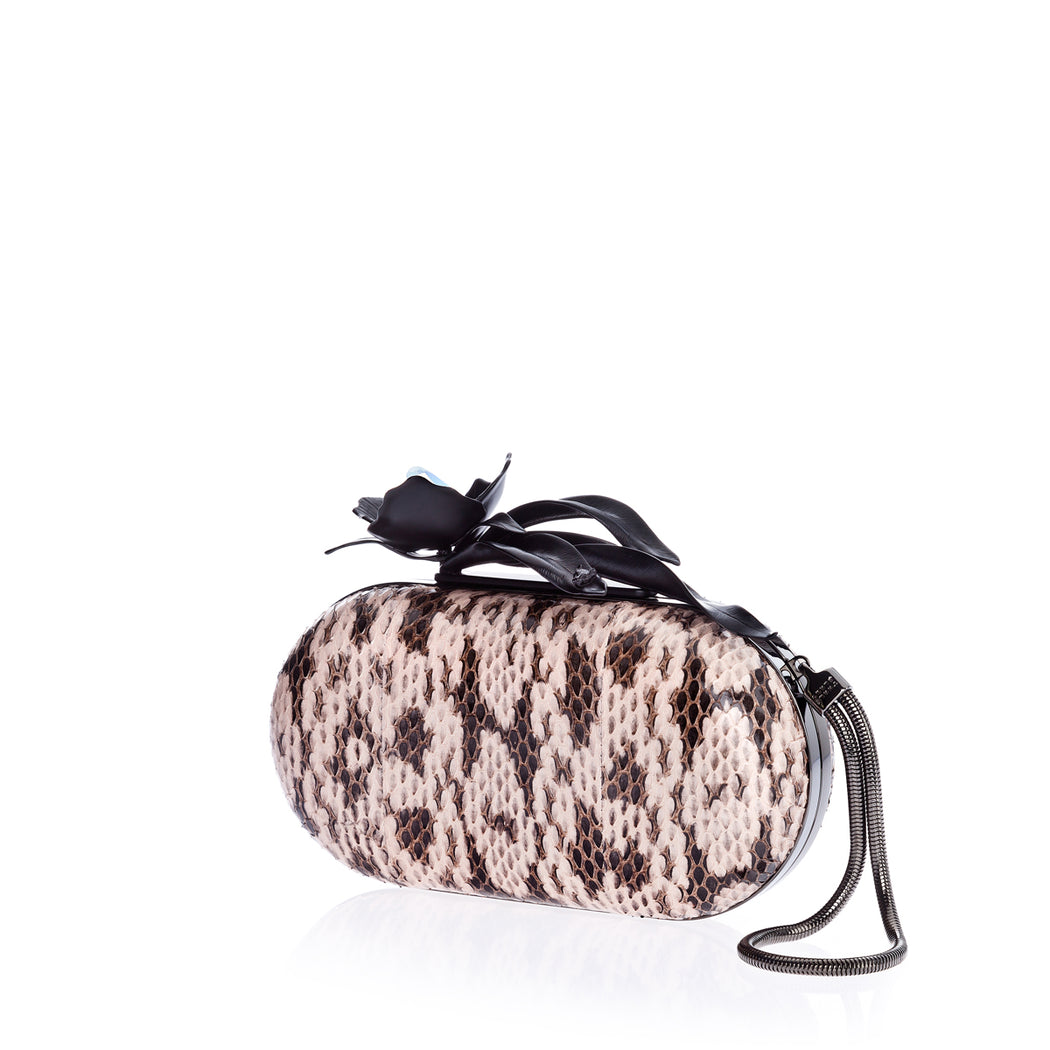 This elegant clutch bag in nude elaphe has delicate detailing on the petals and leaves, embellished with a single iridescent stone. Shown with detachable wrist chain that is included. Designed to fit just the essentials. Handmade in Italy.