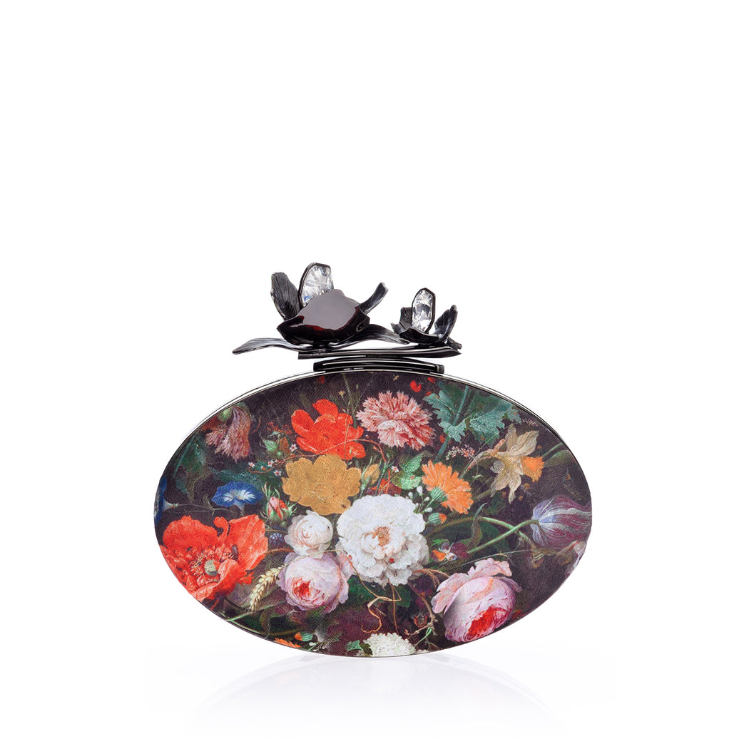 An edgy luxury evening clutch in Bouquet Silk Jacquard, the Oval Bloom features a gunmetal orchid and crystal stones. A detachable wrist chain is included. Designed to fit just the essentials.