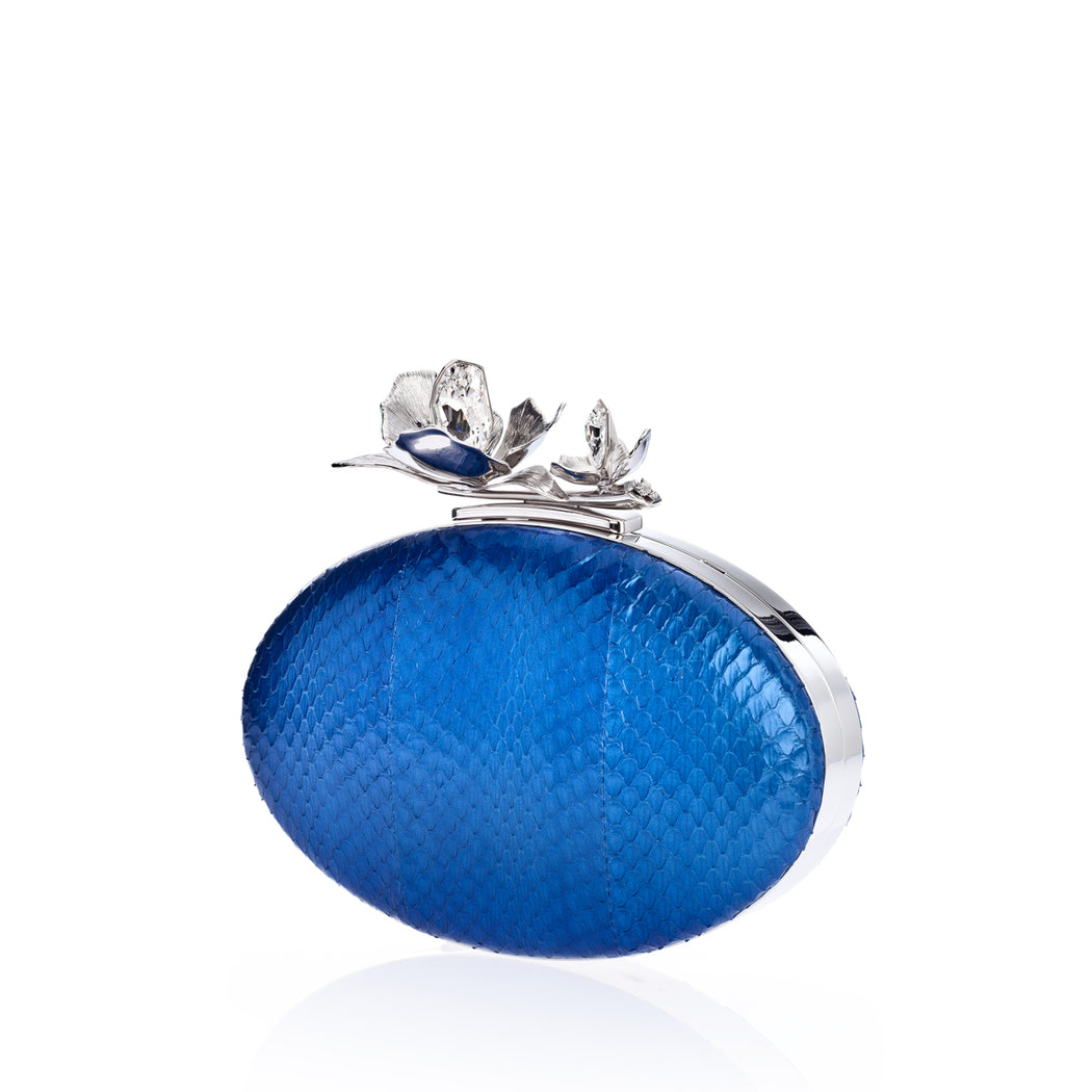 An edgy luxury evening clutch, the Oval Bloom features silver orchid and crystal stones, set against rich cobalt elaphe. A detachable wrist chain is included. Designed to fit just the essentials.
