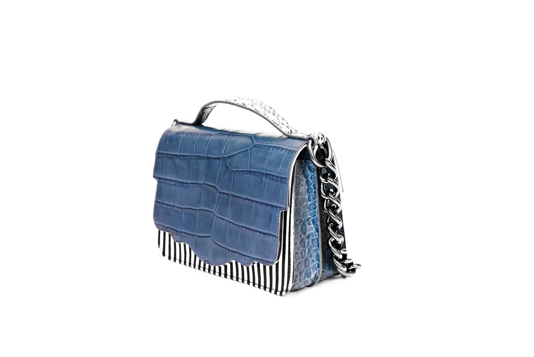 The double-sided Audreyette Mini in black and white striped canvas with denim blue embossed croc and black and white elaphe is a luxury handbag for every day. It's the same petite bag as the original Audreyette Mini, but with double the space. A designer crossbody bag that fits all the essentials. Can be worn as a crossbody or the strap can be doubled and worn on the shoulder. Elaphe top handle adds an extra dimension of texture.