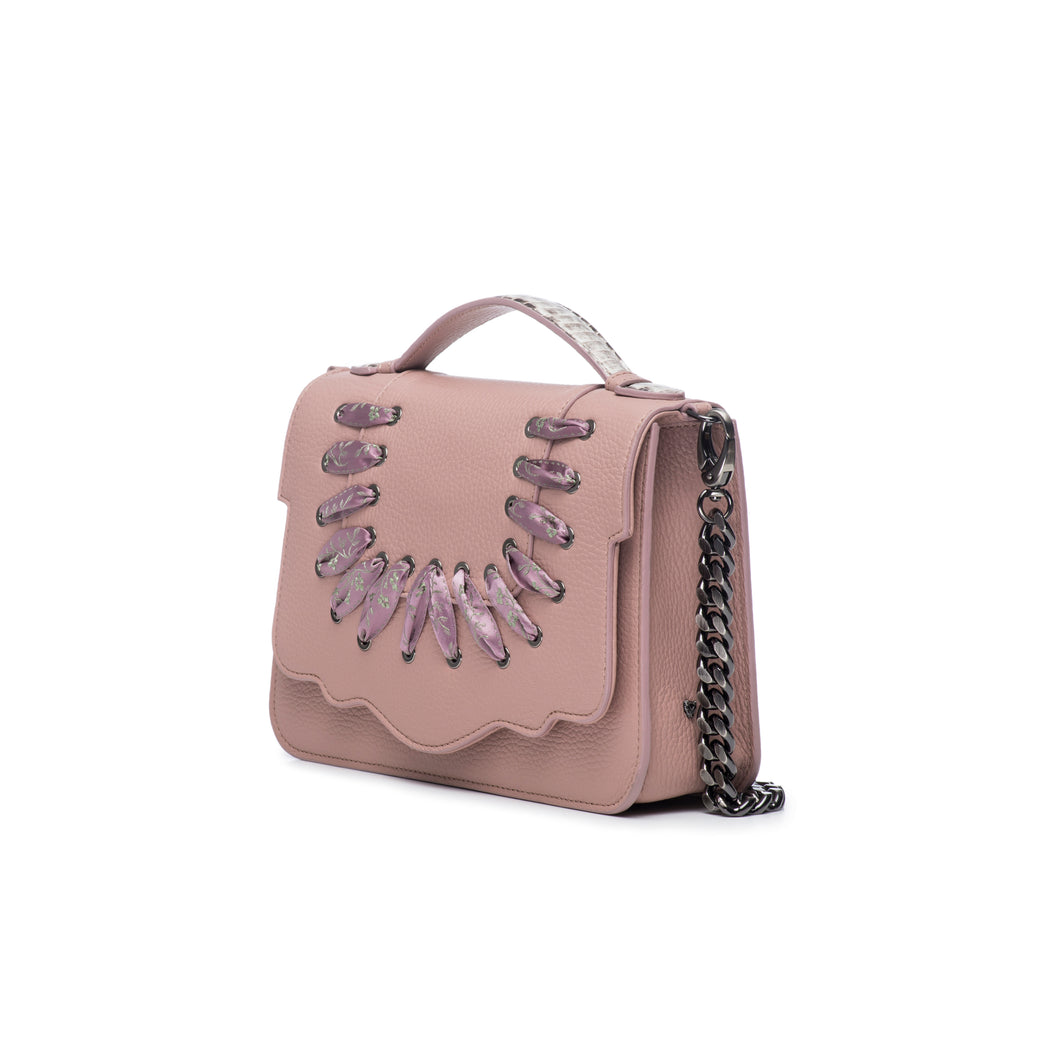 This best-selling top handle luxury leather bag in blush pebbled calfskin features both a detachable crossbody leather strap and a detachable chain strap. Make it your own with a fur Duma Hok-Pom or our signature leather tassel or opt for one of our leather guitar straps for an on-trend look. It is one of the easiest to accessorize handbags.