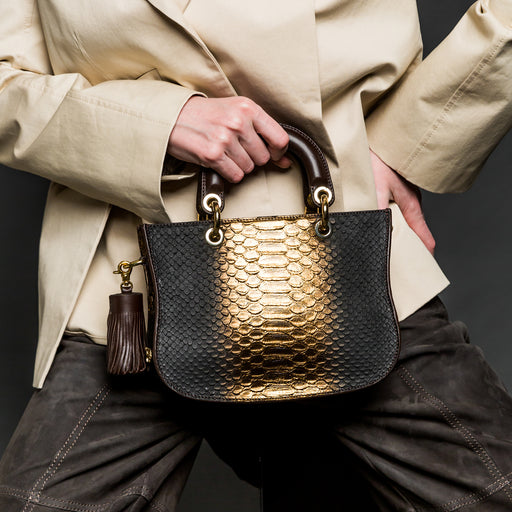 Woman holding a designer satchel in metallic gold & brown snakeskin embossed leather